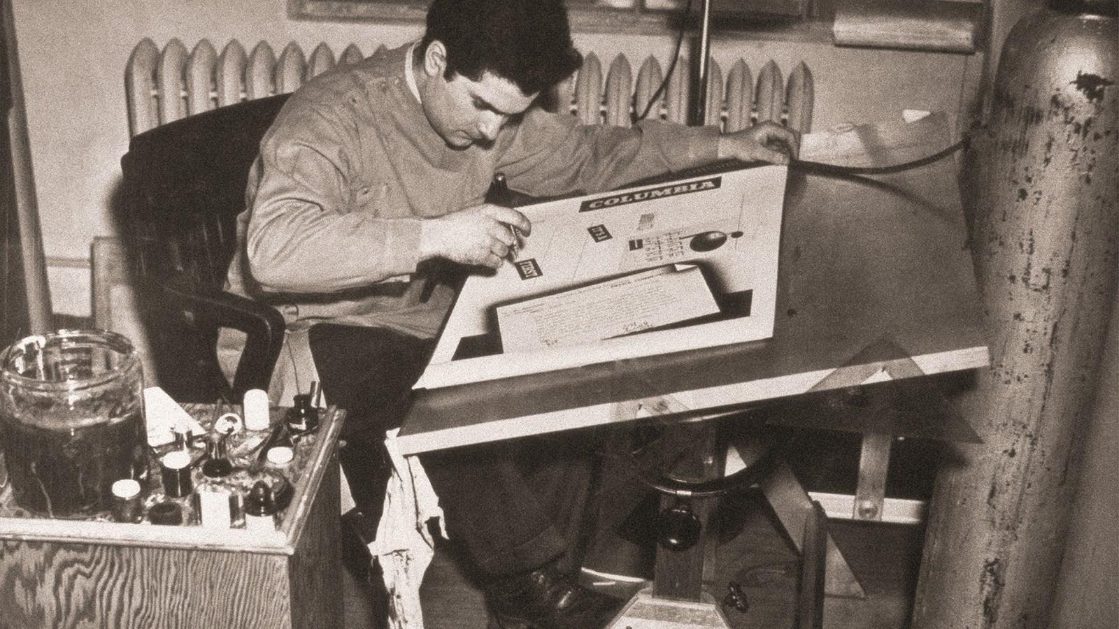 Steinweiss en plein travail chez Columbia Records, Bridgeport, Connecticut, 1939. On voit à droite les bonbonnes d'air comprimé alimentant l'aérographe. Un outil qu'utilisait beaucoup Steinweiss pour coloriser ses créations et qui a largement marqué l'esthétique de l'époque.